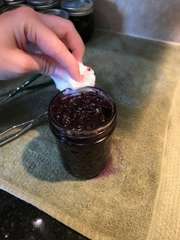 Cleaning rim of Blueberry Butter in jars to process
