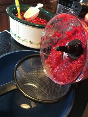 Pour cranberry puree into a strainer